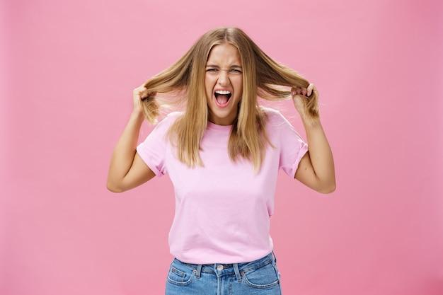 Portret van boos verontwaardigde en geïrriteerde vrouw die zich onder druk gezet voelt, schreeuwend en haar uit het hoofd trekt, staande geïrriteerd over roze achtergrond