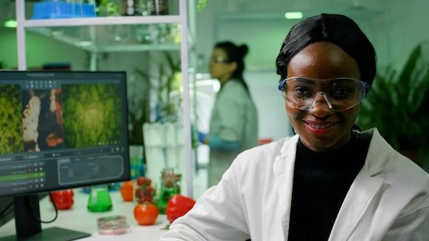 Portret van botanicus afrikaanse vrouw die werkt in een microbiologisch laboratorium dat biologische landbouw ontwikkelt
