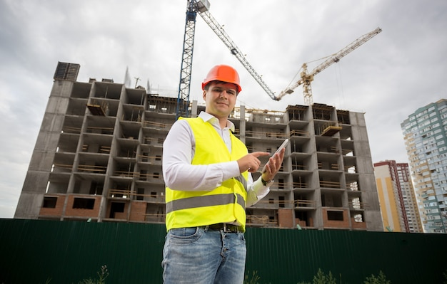 Portret van bouwinspecteur met digitale tablet op bouwwerf