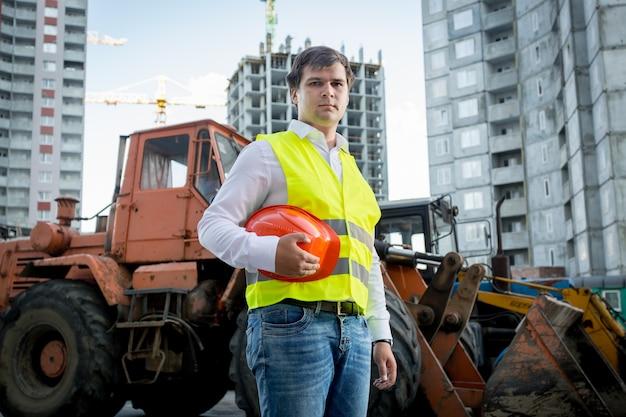 Portret van bouwinspecteur poseren naast graafmachine op bouwplaats