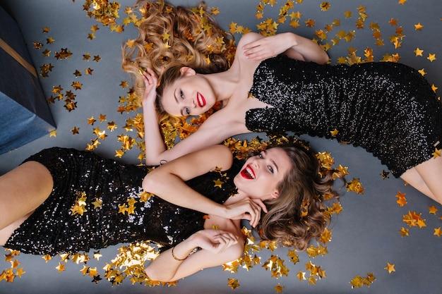 Portret van bovenaf twee modieuze jonge vrouwen die in gouden tinsels leggen. luxe zwarte jurk, rode lippen, lang krullend haar, opgewekte stemming, plezier maken, glimlachen, prachtige modellen.