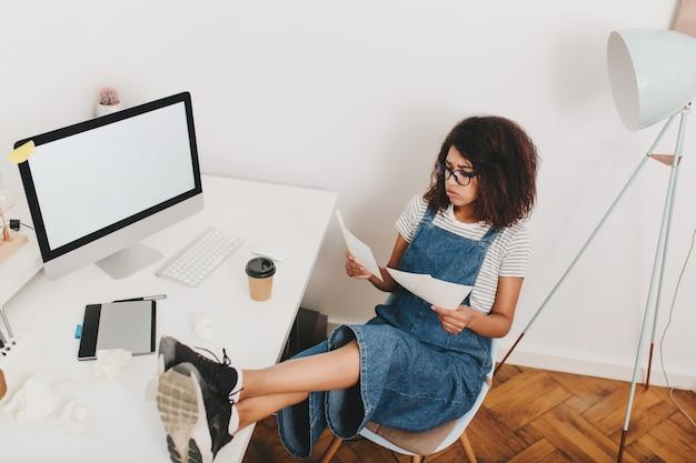 Portret van bovenaf van drukke jonge vrouw in glazen zittend met benen op tafel naast computer en tablet