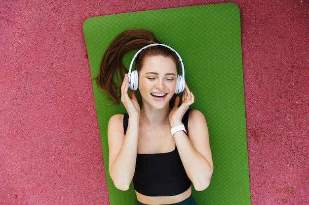 Portret van bovenaf van een aantrekkelijke sportvrouw die een trainingspak en een koptelefoon draagt die op een fitnessmat ligt tijdens de training op het sportveld