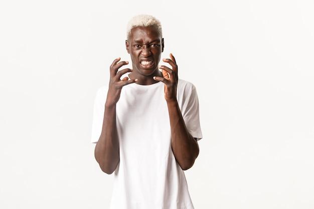 Portret van boze afro-amerikaanse blonde man, balde handen en hatelijk kijken, verontwaardigd of gehinderd