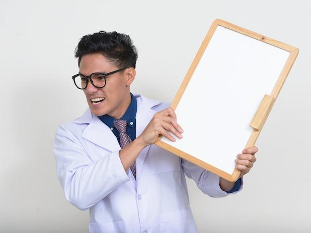 Portret van boze aziatische man arts met een bril met wit bord