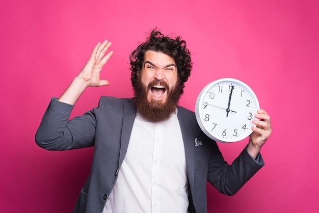 Portret van boze bedrijfsmens die en klok, vertragingsconcept schreeuwen houdt