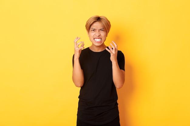 Portret van boze en pissige aziatische blonde kerel