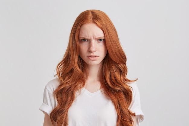 Portret van boze fronsende jonge vrouw met lang golvend rood haar draagt t-shirt ziet er gek uit