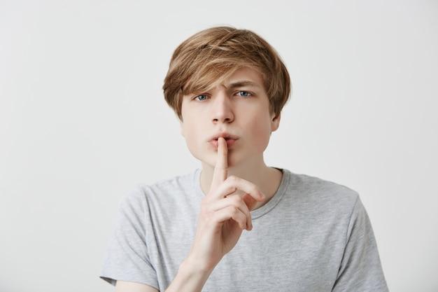 Portret van boze geïrriteerde blonde man vraagt vertrouwelijke informatie geheim te houden, geïrriteerd door roddels, vraagt stil, zegt: stil, stop met praten. blanke man maakt stilte gebaar