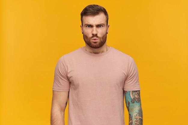 Portret van boze knappe getatoeëerde jongeman in roze t-shirt met baard kijkt gespannen en geïrriteerd over gele muur staan en kijken naar de voorkant