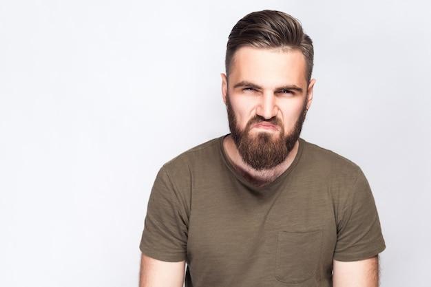Portret van boze trieste bebaarde man met donkergroen t-shirt tegen lichtgrijze achtergrond. studio opname. .