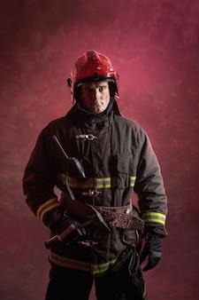 Portret van brandweerman in uniform op donkerrood