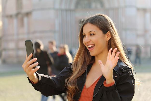 Portret van braziliaanse vrouw die videotelefoneren met behulp van slimme telefoon in stadsstraat