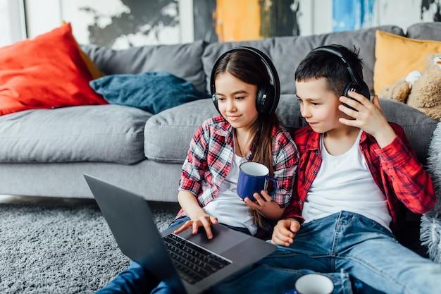 Portret van broer en zus kijken naar grappige film met koptelefoon, terwijl het gebruiken van laptop