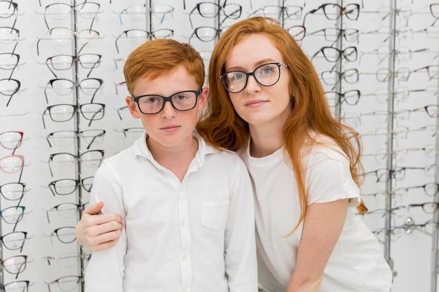 Portret van broer en zus met spektakel in optica winkel