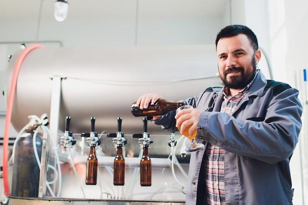 Portret van brouwer die bier op zijn werkplaats in brouwerij maakt