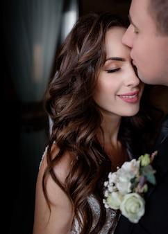 Portret van bruid en bruidegom waanzinnig verliefd op gesloten ogen, trouwdag, trouwfoto