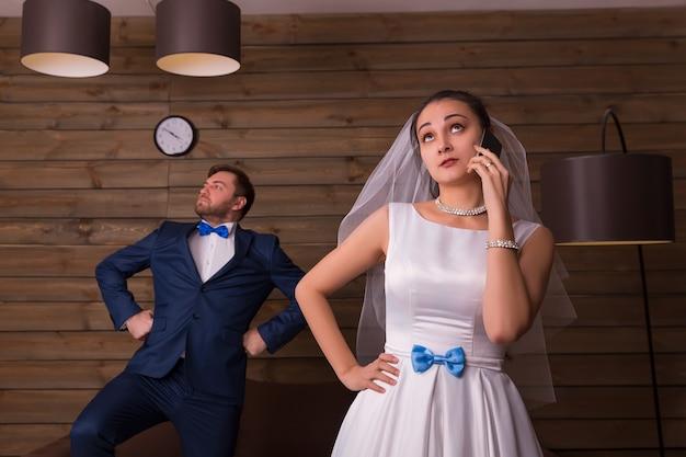 Portret van bruid met behulp van mobiele telefoon en bruidegom poseren op houten kamer