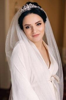 Portret van bruid met chique bruidssluier en diadeem. bruid in witte badjas kijkt naar de camera.