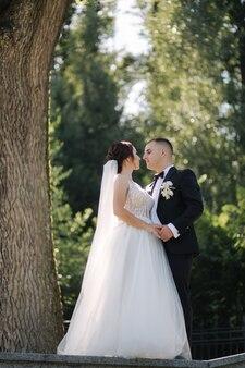 Portret van bruidegom en bruid buiten in de zomertijd. elegante vrouw met stijlvolle echtgenoot in park