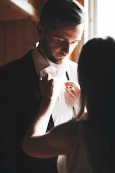 Portret van bruidegom gekleed door zijn bruid in de buurt van een raam close-up.