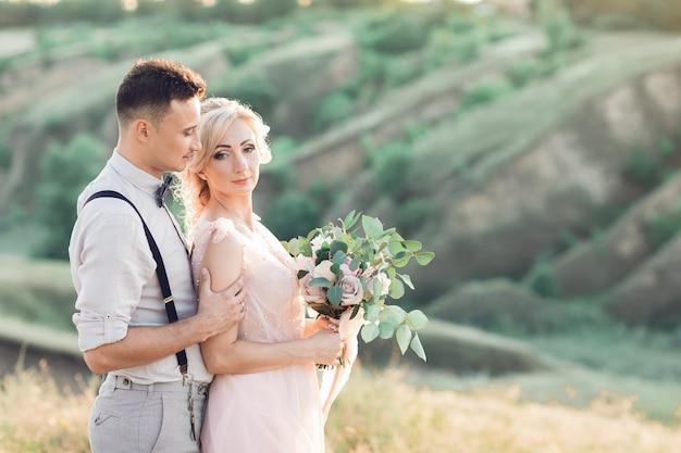 Portret van bruidspaar over de aard in zomerdag. de bruid en bruidegom knuffelen op de bruiloft. fijne kunst