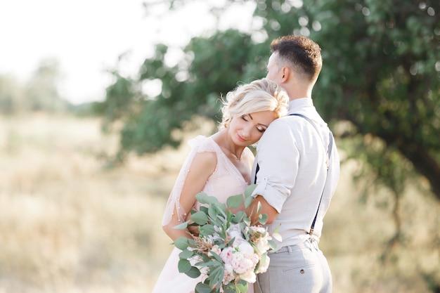 Portret van bruidspaar over de aard in zomerdag. de bruid en bruidegom knuffelen op de bruiloft.