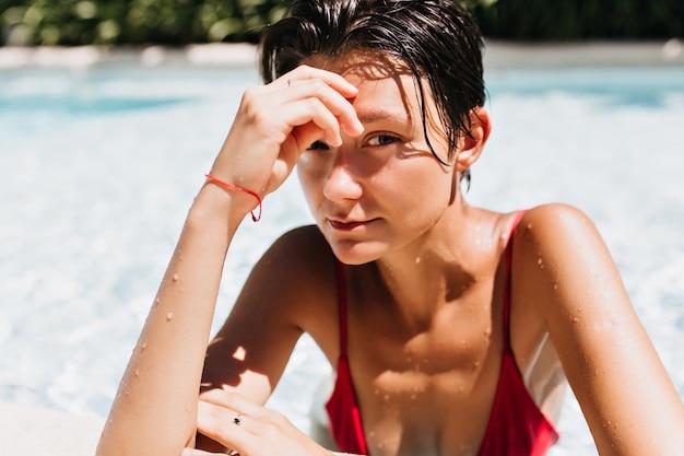 Portret van bruinharige vrouw met gebruinde huid ontspannen in zwembad.