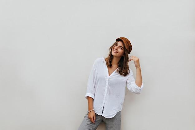 Portret van bruinogige kortharige vrouw in bruin fluwelen hoed, oversized blouse en grijze broek op witte ruimte.