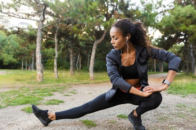 Portret van brunette afrikaanse amerikaanse vrouw 20s die zwarte trainingspak draagt die oefeningen doet, en haar benen in groen park strekt