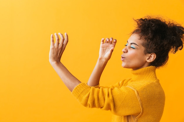 Portret van brunette afrikaanse amerikaanse vrouw die met afrokapsel door onzichtbare geïsoleerde kijker kijkt