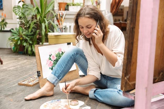 Portret van brunette artistieke vrouw zittend op de vloer en praten op mobiele telefoon tijdens het tekenen van foto op papier met verfpalet in workshop of masterclass