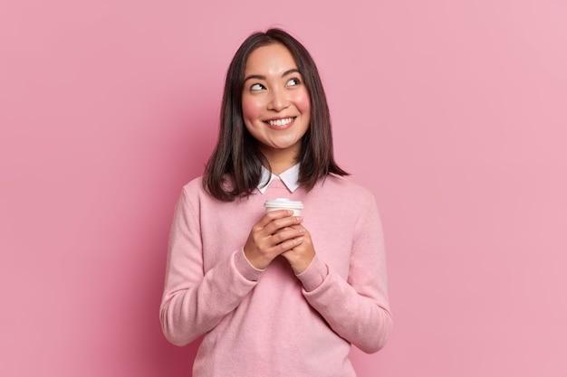 Portret van brunette aziatische vrouw met dromerige uitdrukking glimlacht aangenaam dagdromen met afhaalmaaltijden koffie draagt nette roze trui vormt binnen. nadenkend vrouwelijk model voelt goed