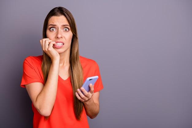 Portret van brunette dame in rood t-shirt poseren tegen de paarse muur met telefoon