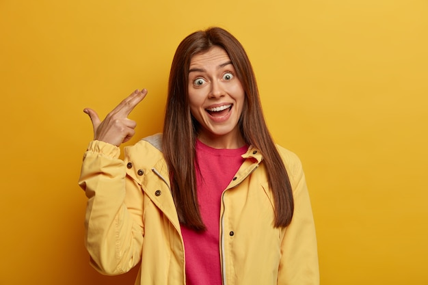 Portret van brunette europese vrouw heeft uitdrukking verbaasd, lacht en maakt vinger pistool pistool gebaar, schiet in de tempel, dwazen rond als verveeld voor lang wachten, draagt gele jas