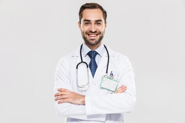 Portret van brunette jonge arts met stethoscoop glimlachend en permanent met armen gekruist geïsoleerd over witte muur