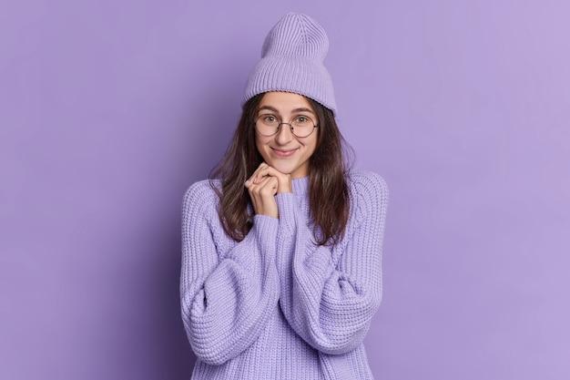 Portret van brunette jonge europese vrouw houdt handen onder de kin glimlacht zachtjes heeft tedere uitdrukking draagt ronde bril stijlvolle hoed en trui.