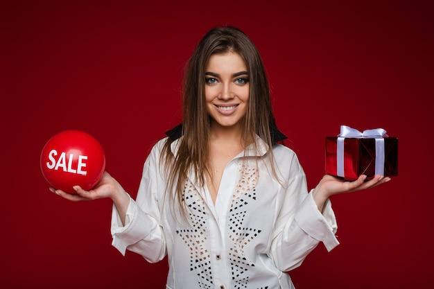 Portret van brunette kaukasisch meisje in wit overhemd met een geschenk in de ene hand en een rode bal met verkoopwoord in de andere hand, glimlachend in de camera. knipsel op rode achtergrond.