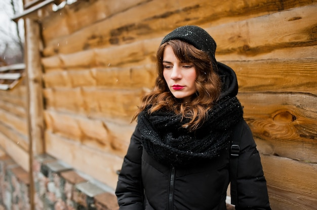 Portret van brunette krullend meisje in zwarte jas, muts en sjaal op winterdag.