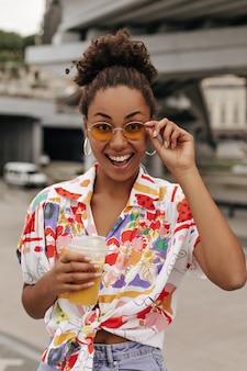 Portret van brunette krullende vrouw in stijlvolle kleurrijke blouse verheugt zich, houdt jus d'orange vast en zet een zonnebril af