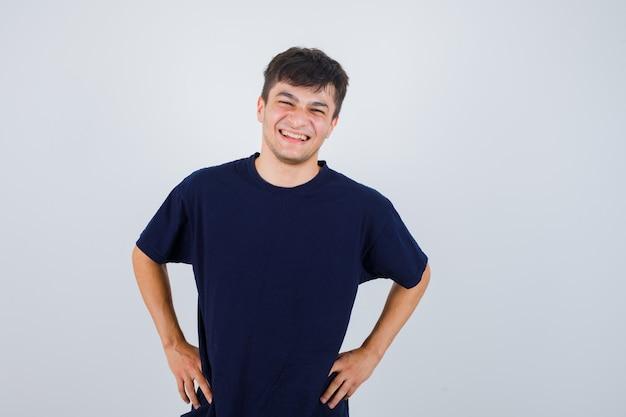 Portret van brunette man camera kijken, houdt handen op taille in donkere t-shirt en op zoek vrolijk, vooraanzicht.