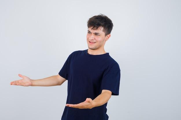 Portret van brunette man vragen vraag gebaar maken in donkere t-shirt en op zoek attent.