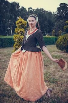 Portret van brunette vrouw gekleed in historische barokke kleding met ouderwets kapsel, buitenshuis. middeleeuwse jurk uit de middenklasse