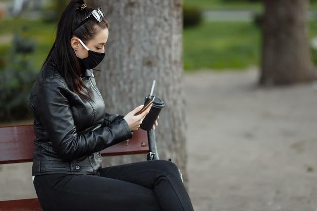 Portret van brunette vrouw in een zwart beschermend masker zittend op een bankje in het park, zonnige lentedag. vrouw praten over mobiele telefoon.