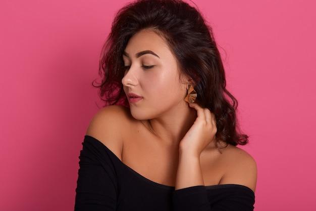 Portret van brunette vrouw met golvend haar poseren met de handen in de nek en opzij kijken, het dragen van een zwart shirt met blote schouders, geïsoleerd over roze muur.