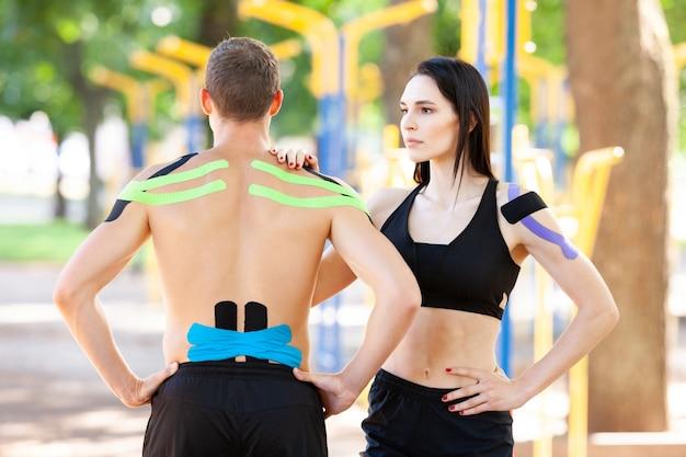 Portret van brunette vrouw met hand op schouder van onherkenbare man, professionele kaukasische atleten met kinesiologische taping op lichamen