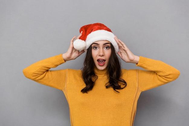 Portret van brunette vrouw met santa claus rode hoed glimlachend en plezier hebben, geïsoleerd over grijze achtergrond