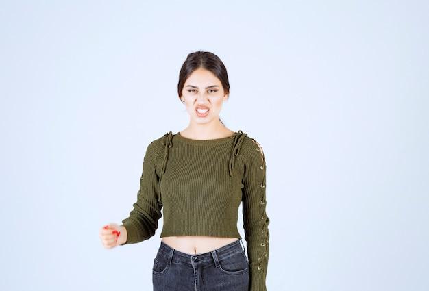 Portret van brunette vrouw permanent en boos gezicht tonen op witte achtergrond.