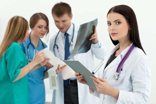 Portret van brunette vrouwelijke geneeskunde arts documentmap met drie haar collega's te kijken naar cardiogram en x-ray foto. gezondheidszorg en geneeskunde concept.