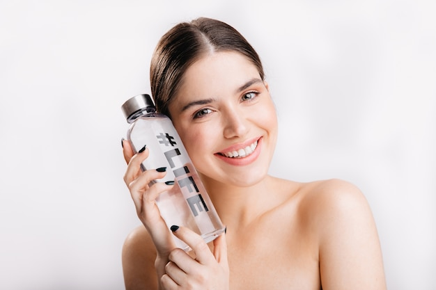 Portret van brunette zonder make-up in geweldige sfeer op geïsoleerde muur. positieve vrouw met een gezonde huid poseren met fles water met hashtag leven.